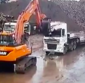 Excavator driver smashes Two Lorry's in yard